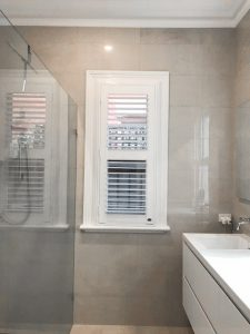 Skinny Long Bathroom Window with White Plantation Shutters