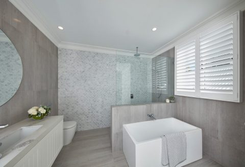 Plantation shutters above luxury bathtub